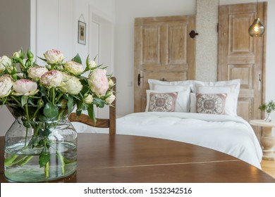 Fresh roses flowers on wooden table in modern bedroom