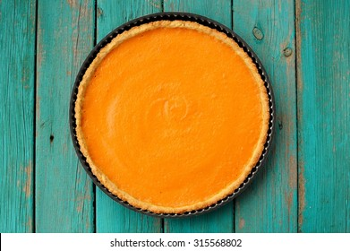 Fresh round bright orange homemade pumpkin pie in baking dish on turquoise table