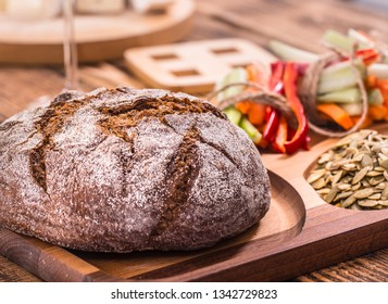 A fresh round of dark bread on a wooden plate , the concept of healthy food