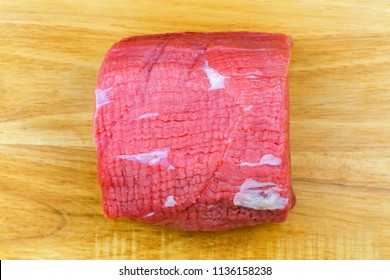 Fresh Round steak, beef steak from the eye of round, rear leg meat of cow without round bone, femur. Top view on wooden background