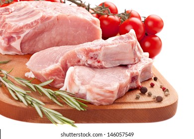 fresh row pork  with rosemary and spices on wood board isolated on white