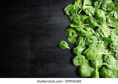 Fresh row spinach on black background. Top view. Space for text