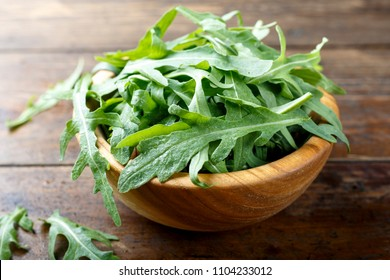 fresh rucola salad on a wooden background. place for text.