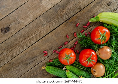 Fresh rustic vegetables on an old wooden table - tomatoes, cucumbers, onions, dill, beans. Delicious healthy ingredients for a healthy diet.