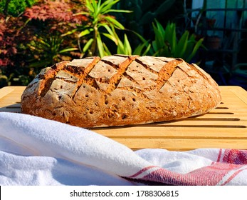the fresh rye bread lies on the garden table to cool off - Shutterstock ID 1788306815