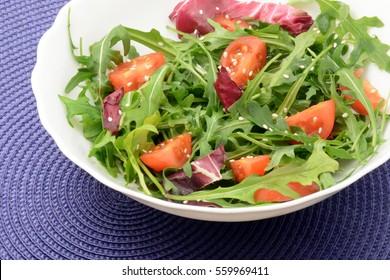 Fresh salad with arugula cherry tomatoes and sesame