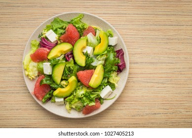 Fresh salad with avocado and fruits on a wooden table. Tasty morning breakfast. healthy diet food