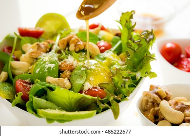 fresh salad with avocado, nuts, sesame leaves and sour dressing