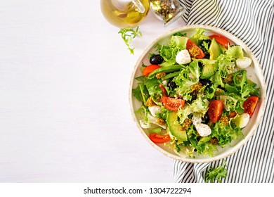 Fresh salad with avocado, tomato, olives and mozzarella  in a  bowl.  Fitness food. Vegetarian meal. Top view