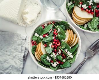 Frischer Salat mit Babyspinat, Birne, Granatapfelkäse und Hüttenkäse. Zwei Schüsseln mit köstlichem Sommerfruchtsalat auf Marmortisch. Leerzeichen für Text kopieren. Ideen und Rezepte für gesundes Frühstück oder Mittagessen