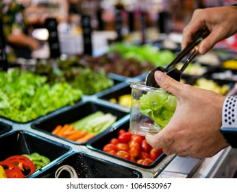 Fresh Salad bar counter with person's hands lifting vegetable into a salad bowl for healthy and diet meal for vegetarian person with smooth light and shadow.