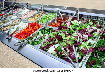 Fresh salad bar with various fresh assortment of ingredients. Display space of options for choice of clients in supermarket or restaurant