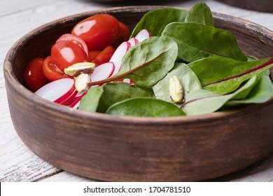 Boul de salade fraîche aux feuilles vertes de blette, radis tranché, tomates cerises et pistaches. Un repas végétalien sain dans un bol en céramique sur une table rustique, une salade verte à base de plantes