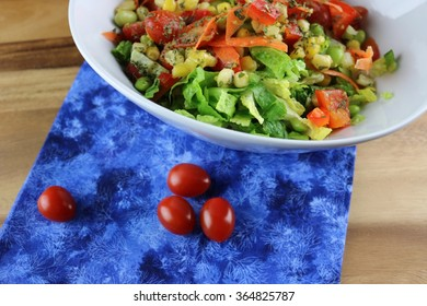 Fresh salad in a bowl on a blue napkin