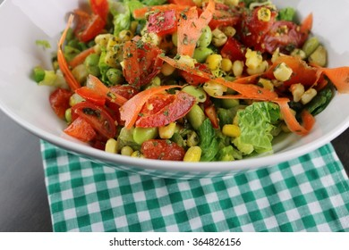 Fresh salad in a bowl on a checker napkin close up