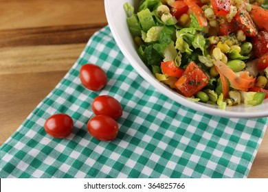 Fresh salad in a bowl on a flower napkin with cherry tomatoe