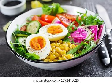 Fresh salad. Bowl with fresh raw vegetables - cucumber, tomato, watermelon radish, lettuce, arugula, corn and boiled egg. Healthy food. Vegetarian buddha bowl.