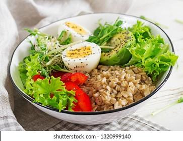 Fresh salad. Breakfast bowl with oatmeal, paprika, avocado, lettuce, microgreens and boiled egg. Healthy food. Vegetarian buddha bowl.