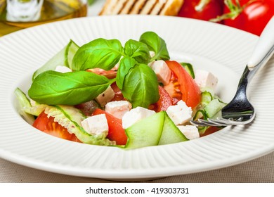 Fresh salad of cheese, tomato, cucmber, onion and basil.