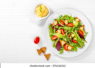 fresh salad of cherry tomatoes,croutons and capelin roe, mixed lettuce leaves in a white dish on an old wooden table, top view