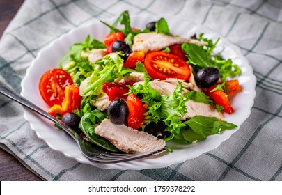 Fresh salad with chicken breast, arugula, black olives,red pepper, lettuce, fresh sald leaves and tomato on a white plate on wooden table background