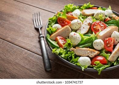 Fresh salad with chicken breast, mozzarella  and tomato. Top view