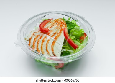 Fresh salad with chicken breast in plastic box isolated on a white background.  Salad for take away or food delivery