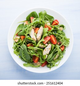 Fresh salad with chicken, tomato and greens (spinach, arugula) on blue wooden background top view. Healthy food.