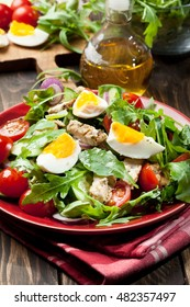 Fresh salad with chicken, tomatoes, eggs and arugula on plate. Healthy food