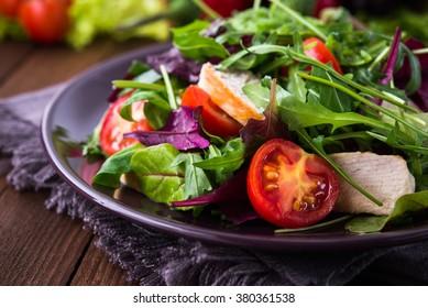 Frischer Salat mit Huhn, Tomaten und gemischten Grünen (Arugula, mesclun, mache) auf Holzhintergrund, Nahaufnahme. Gesundes Essen.