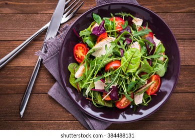 Fresh salad with chicken, tomatoes and mixed greens (arugula, mesclun, mache) on wooden background top view. Healthy food.