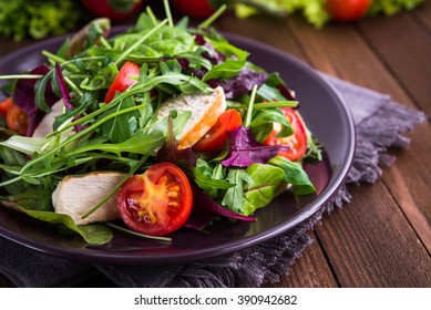 Fresh salad with chicken, tomatoes and mixed greens (arugula, mesclun, mache) on wooden background close up. Healthy food.