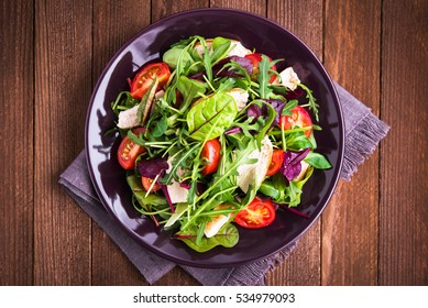 Fresh salad with chicken, tomatoes and mixed greens (arugula, mesclun, mache) on wooden background top view. Healthy food. Meat and vegetables.