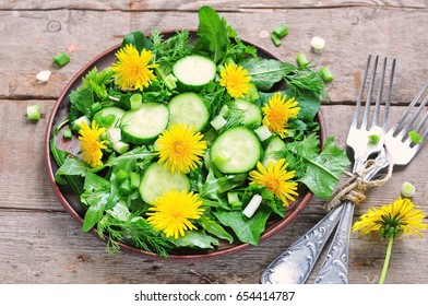 Fresh salad with cucumber, rucola, green onion and dandelion's flowers on wooden background
