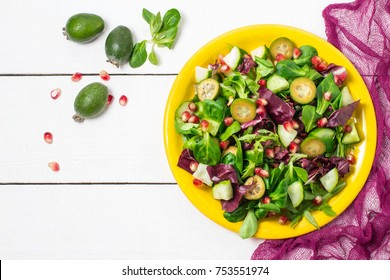 Fresh salad with cucumbers, feijoa, pomegranate seeds and green lettuce leaves. Served with vinaigrette sauce. Concept of diet and healthy food. Top view