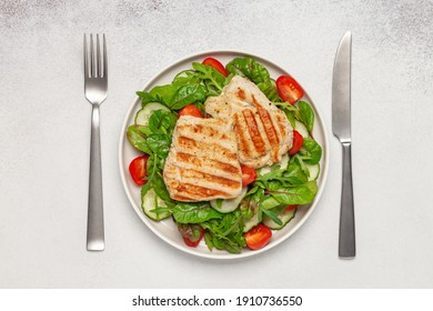 Fresh salad - cucumbers, tomato, arugula, chards leaves and chicken fillet grill in a plate on the table. Top view. Healthy diet food.
