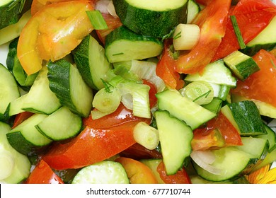 Fresh salad of cucumbers, tomatoes, greens and vegetable oil