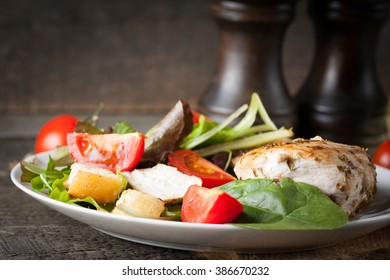 Fresh salad with delicious chicken breast, ruccola, spinach, cabbage, arugula and tomato on wooden background. Oil, salt and pepper.