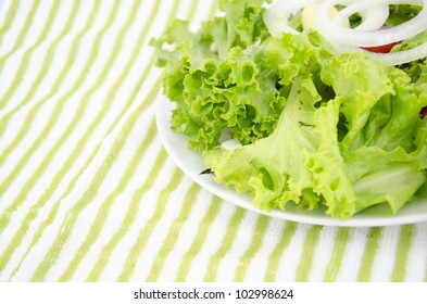 Fresh salad is in a dish on a green background