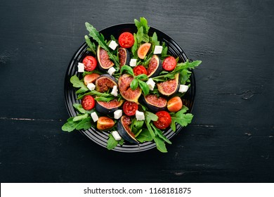 Fresh salad with figs, arugula leaves, cherry tomatoes and feta cheese. Free space for text. Top view.