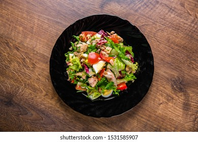 Fresh salad with fish, arugula, eggs,red pepper, lettuce, fresh sald leaves and tomato on a black plate on wooden table background