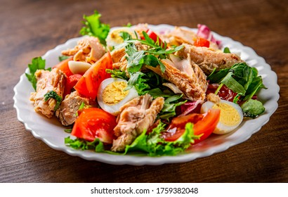 Fresh salad with fish, arugula, eggs,red pepper, lettuce, fresh sald leaves and tomato on a white plate on wooden table background