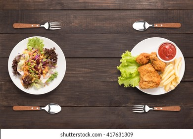 Fresh salad and Fried chicken and french fries on the wooden background. contrasting food.