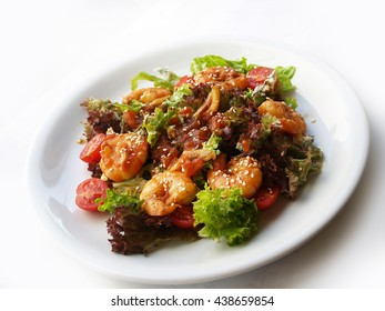 Fresh salad with fried shrimp, cherry tomatoes, sesame seeds and a light spicy sauce
