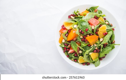 Frischer Salat mit Früchten und Grün auf weißem Hintergrund Draufsicht mit Platz für Text. Gesunde Lebensmittel.