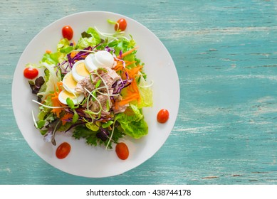 Fresh salad with fruits and greens on vintage wooden background top view with space for text.