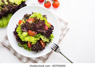 Fresh salad with green and purple lettuce, tomatoes and cucumbers on white wooden background top view. Healthy food.