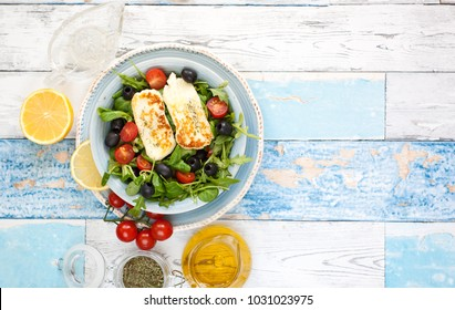 Fresh salad with halloumi cheese on blue textured background