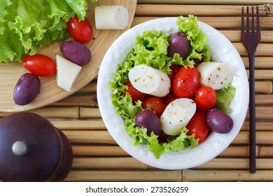 Fresh salad of heart of palm (palmito), cherry tomatoes and olives on white plate with black pepper and wooden fork on bamboo. Selective focus