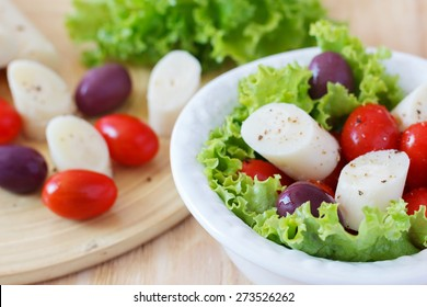 Fresh salad of heart of palm (palmito), cherry tomatoes and olives on white plate. Selective focus